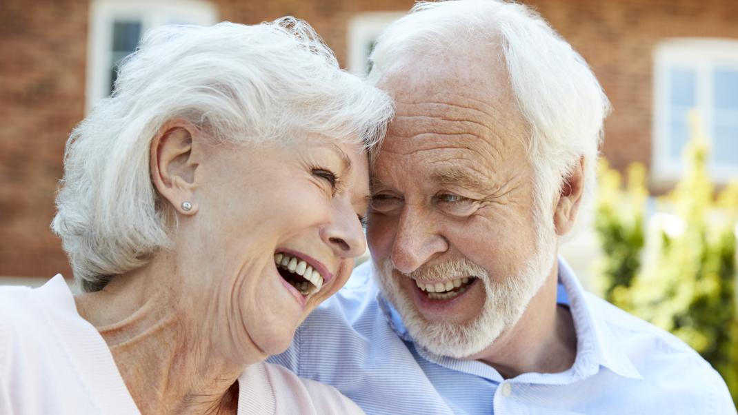 Elderly couple smiling at assisted living home